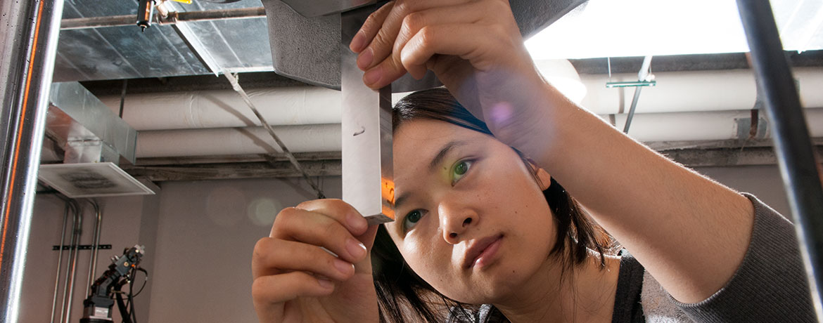 researcher closely evaluating a metallic material