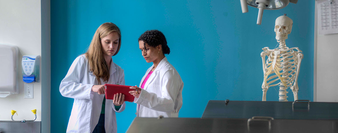 two students in lab coats studying a patient file in a lab