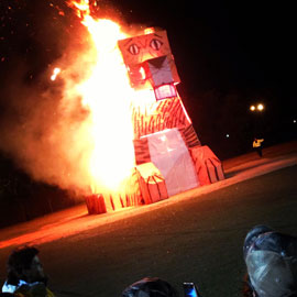 A large tiger made by engineering students ablaze while spectators watch.
