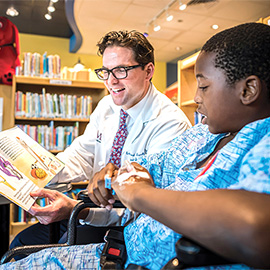 Dr. Buchanan and a young boy dressed in a hospital gown reading a book