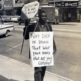 1960s civil rights protestor carries signs denouncing segregation