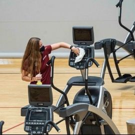 A student employee at one of the campus gyms sanitizing exercise equipment