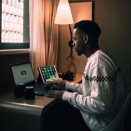 A UofSC student sitting at his desk in a dimly lit room. He has an iPad to his right and his laptop opened in front of him on the Google homepage