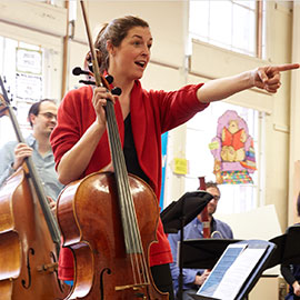 School of Music assistant professor Claire Bryant holds a cello while pointing at a fellow musician.