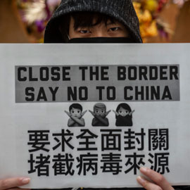 protester holds sign calling to close the border